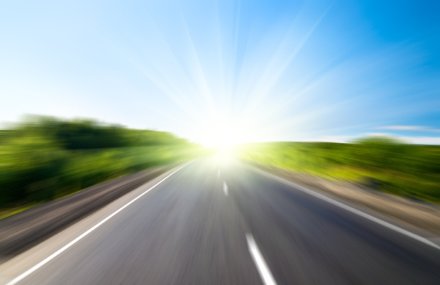bigstock-motion-blur-road-and-sun-12744857